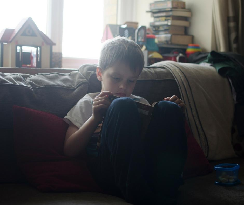 child reading a book on sofa