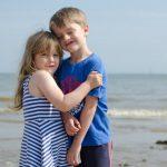 Siblings hugging on a beach