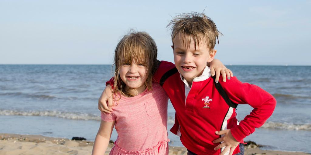 Siblings on a beach with arms round each other